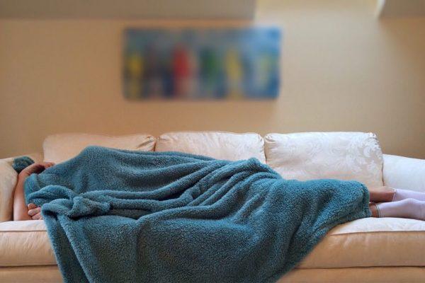 foto_slapen_op_de_bank_onder_blauw_deken